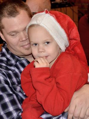 Morgan Greberg sitter hellre i pappa Roberts knä än att plocka figurer till julkrubban.