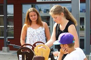 Skidskyttarna Sara Östling och Hanna Carlström hjälper en möjligen blivande skidskytt att provskjuta på tisdagens marknad i Sveg.