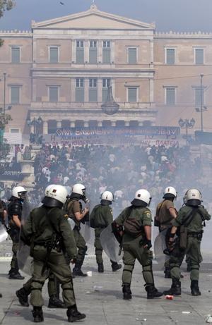 Krisens epicentrum. Poliser bevakar demonstrationerna på Syntagmatorget i Aten. I bakgrunden syns parlamentsbyggnanden.    FOTO: SCANPIX