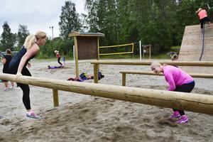 Under och över bommar klättrar Stina Eklid och Rebecca Braun.