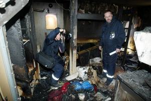 Polisens tekniker Mats Falkdalen och Tommy Mälberg tittar närmare på den brandhärjade lägenheten.