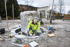 Stenläggare Björn Wedin lägger sista handen på sargen till dammen runt fontänen.