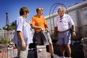 Lars Mobacke hjälper Hildegard och Rolf Philipson att hitta en fin sten till dammen de nyligen har anlagt i sin trädgård.