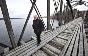 Anders Holmstedt, antikvarie på länsstyrelsen, på väg över en av broarna.
