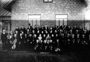 Godtemplarlogens och arbetareföreningens orkestrar slogs ihop till bruksmusikkåren. Här poserar musikkåren utanför Föreningslokalen. Året är 1898.