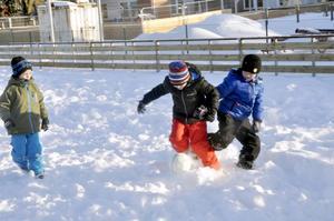Med liv och lust spelar killarna fotboll på den snöiga planen.