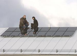 Stig Nordvall och Annika Magnusson på Bollnäs Bostäder visar modigt de nya solcellerna högt uppe på taket.
