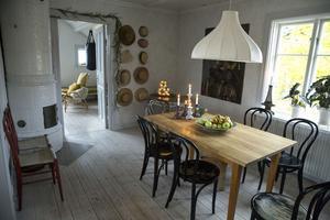 Det rymliga köket som ligger på övervåningen rymmer både köksö, vedspis och matplats. På en av matrummets väggar har Mikaela en samling med hattar från olika resor.