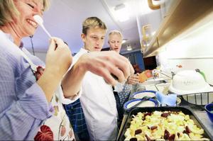 Eva Peterson arbetar på Fjällripan. Tillsammans med kocken Johan Gavlin kryddar hon rotsaker som ska bli ugnsrostade tillsammans med kikärter.  I bakgrunden syns Janne Olsson.