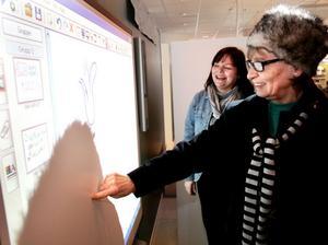 Bibliotekschefen Helene Swenne visar den nya digitala skrivtavlan, som förutom är en interaktiv griffeltavla också kan erbjuda videokonferenser och internetanvändning. Biblioteksbesökaren Ingrid Eriksson var först ut att prova tekniken.