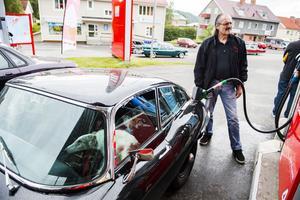 Bjarne Svendsen från Hudiksvall tankar sin Jaguar E-type-69, borzoien Alexeij väntar tålmodigt i framsätet.