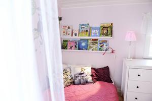 Ett draperi med ljusslingor fixar en ombonad känsla för sänghörnan i Stellas rum.