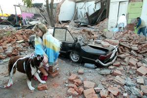 En kvinna sitter framför ett hus som raserats i jordbävningen i Talca i Chile.  BILD: SCANPIX