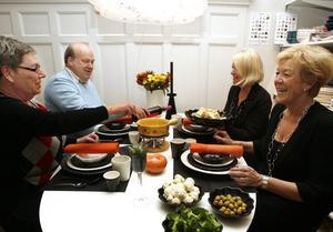 """FONDUE PÅ TAPETEN. Det är trendigt med orange i inredning och trendigt att äta fondue igen. För att matcha Ostbutikens finduegryta bad Tethas mat                                   """"Sofftaflickorna"""" att få duka till fonduekväll i den gemensamma butiken Soffta i Gävle. Ostbutikens ägare Mona låter sig väl smaka medan maken och medarbetaren Ulf, serverar  Vanja Bengtsson och Margaretha Järverud                                      """"rödtjut""""."""