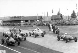 Ett foto från 1950 och starten av TT-loppets tävling för midgetbilar klass F3. leder i starten på Österbyvägen gör engelsmannen Stan Coldham.