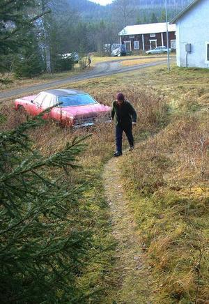 På väg till utedasset passeras en i marken delvis nedsjunken Chevrolet tillhörig Göran.
