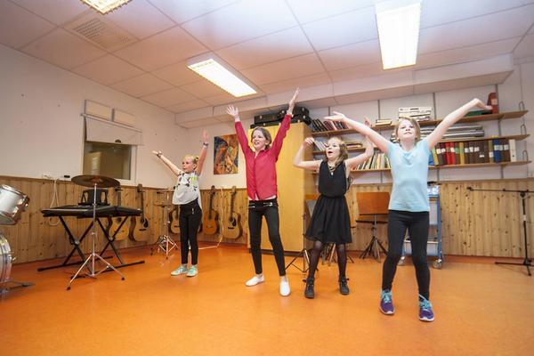 Fyra ivriga elever övar inför kvällens framträdande med YMCA-dans