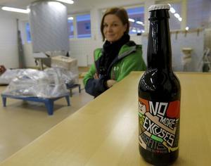 I bakgrunden, en av fyra jästankar. I förgrunden en flaska med bryggeriets etikett.