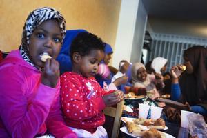 Fadumo Raage, 8, och lillasyster Ifrah, 2, äter gott när fastemånadens slut firas i den muslimska högtiden eid al-fitr.