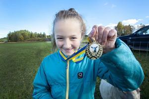 Elin Arvidsson visar stolt upp guldmedaljen som hennes får Sota.