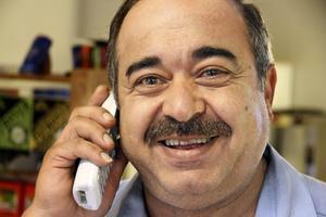 Essam Alswiri pratar med sin far i telefonen. Föräldrarna är bosatta i Syrien, men hälsar vid det här tillfället på Essams bror i Belgien.