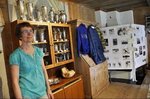 Dottern Elisabeth Modigh har sammanställt utställningen om Melcher Risberg. På bilden syns en del av hans stora prissamling, och hans OS-kläder.