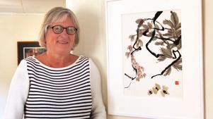 """Anita Hillgren Grandert, ordförande i Roslagens konstnärsgille, vid sitt verk """"Tre flygfän"""" som hon målat med kinesisk tusch på rispapper."""