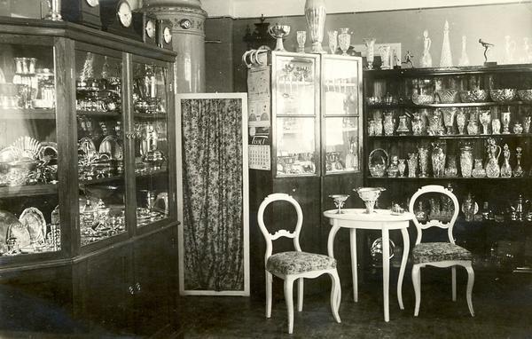 År 1923. Kakelugnen sprider värme från sitt hörn och rokokomöbeln ser elegant ut. Bakom glasrutor skymtar kannor och ljusstakar i drivet silver. Glaspjäser från Orrefors och Kosta var populära presenter.