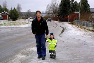 Magnus Swahn och snart fyraårige sonen Simon på promenad på Guldvägen i Forsa. De boende i området begär nu en hastighetsbegränsning eftersom bilar och bussar kör för fort i det barntäta området.