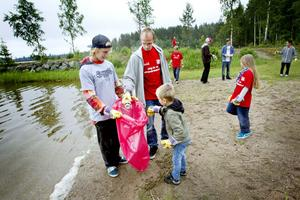 Martin Strömberg håller upp sopsäcken åt far och son Östlin – Anders och Vidar.