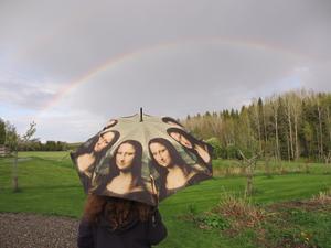 Jag, Gunnel Nordling, står och njuter av regnbågens prakt över Bovallen, under mitt paraplynu i maj månad.