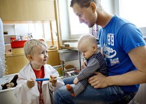 Avgift eller inte? Lille Elias, tre månader, föddes med hjärtfel och har legat inne en tid på barnkliniken på USÖ. Pappa Marcus Pikkarainen tycker att man borde behålla den avgiftsfria akutsjukvården. – Meningen är ju att det ska vara lätt att söka, säger han. Med är också storebror Nils, 3 år, som leker doktor med pappa och lillebror på barnklinikens lekterapi.