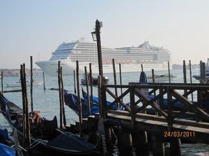Venedig, våren 2011Det är tidig vår och vi har bara någon timma tidigare anlänt till Venedig via lagunen. Nu sitter vi vid kajkanten på Piazzettan och avnjuter en fika i den ljumma vårkvällen. Jag har just fotograferat ett vackert brudpar med de förtöjda gondolerna som bakgrund. Romantiskt!Men vad händer nu? Ljudlöst seglar något jättelikt in. Något som fyller hela lagunen och skymmer all