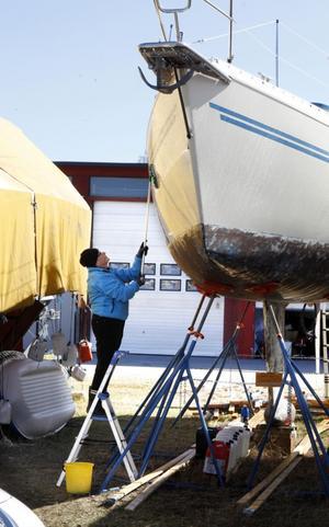 Brita Saarinen tvättar skrovet på båten Two Star.