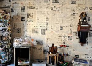 En av väggarna är tapetserad med gamla tidningssidor och det finns telefonkataloger och vykort från sekelskiftet.
