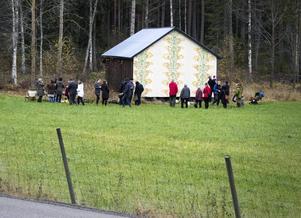 Helena Bratt står bakom den schablonmönstrade laduväggen intill riksväg 50 vid Bollnäs östra infart. Väggen är hennes andra målning och mönstret är hämtat från en tapet som finns i världsarvsgården Gästgivars i Vallsta.