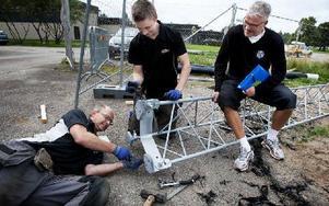 Peter Björk inspekterar när elektrikerna Jörgen Hagberg (liggandes) och Martin Johansson sätter ihop belysningsstolparna. Foto: Peter Ohlsson