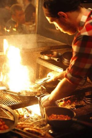 Björkved brinner i såväl eldgrop som vedugn och vedspis  där all mat tillagas. Ingen elplatta, ingen gasspis  bara naturlig värme, sot, aska, rök och eld. Foto: Fredrik Alverland