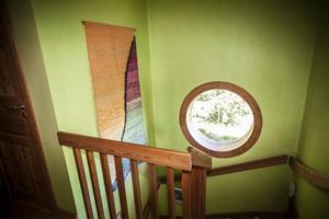Den färgsprakande mattan har Eva själv tillverkat. Det runda fönstret är en kul detalj som ger liv åt båda våningarna.