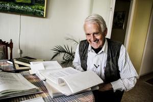 Kjell Grönberg hemma i Delsbo. Framför sig har han allt material rörande kyrkklockan som han samlat på sig genom åren.