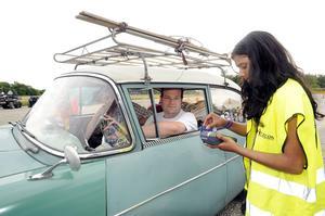 Incheckning. Gerald Wölke och Fred Schiller från Hannover i Tyskland checkar in på Mälarcampingen och välkomnas av Anna Lundin. Gerald Wölke är här för femte gången. Med sig har besökarna ett par skidor som ska med när färden går norrut. Bilen är en Opel 1200 från år 1960. Foto: Alf Pergeman