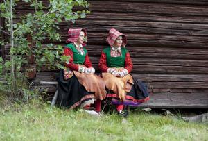 Lill-Karin Gustafsson och Anna-Karin Jobs Arnberg i samspråk framför en timmervägg. Foto:LailaDurán