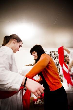 Cajsa Vedin, 18 år, Hudiksvall, som spelar med Enånger/Iggesunds damlag i fotboll, var en av luciatärnorna som provade linnen under tisdagskvällen på Brovallen i Enånger. Monica Pettersson från Enångers luciakommitté hjälpte till med att knyta bandet.