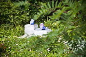Konstnärliga installationer finns överallt i trädgården, och här är det upp och nedvända blomkrukor som fått nya roller som pedestaler.
