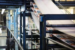 Upp och ner. På vägen upp för trycktornet blir det vita pappret tryckt och på vägen ner ihopvikt, häftad och tillklippt till tidning.