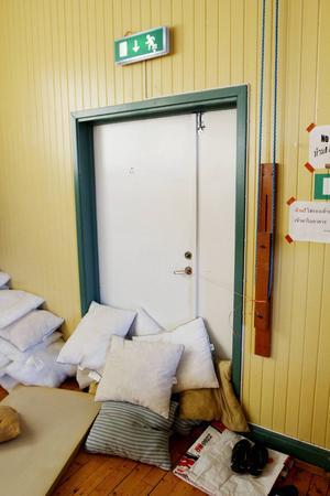 Nödutgången i gamla skolan har knutits fast med ett snöre, eftersom den går upp annars. Och rumänerna har tvingats täta den glappa dörren med kuddar för att inte släppa in kall luft.