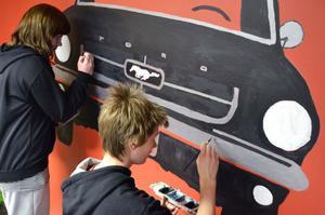 Johanna Jonsson och William Karlsson målar på en bil som numera pryder en vägg i kafeterian.