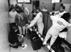 Saneringsgruppen på Forsmark under ledning av Eero Mattilainen (på golvet t. v.) mäter eventuell radioaktivitet på de anställdas kläder i samband med ett misstänkt läckage av radioaktiv strålning från någon av Forsmarks kärnkraftsreaktorer 28:e april 1986. Det visade sig ganska snart att de uppmätta höga värdena av radioaktivt nedfall i stora delar av östra Sverige kom från en härdsmälta i ett kärnkraftverk i Tjernobyl i Sovjetprovinsen Ukraina. Bild: Ingvar Karmhed / SvD / TT / Kod: 11014
