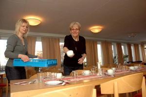 KOPP PÅ PLATS. Carina Vindeland och Maud Eriksson hjälps åt att duka borden.