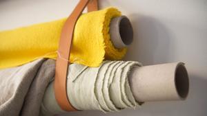Det gäller att hålla koll på alla tygrullar. Att spänna upp dem på väggen frigör golvyta och skapar ordning.
